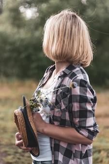 Blondynka w kraciastej koszuli stoi patrzy w dal