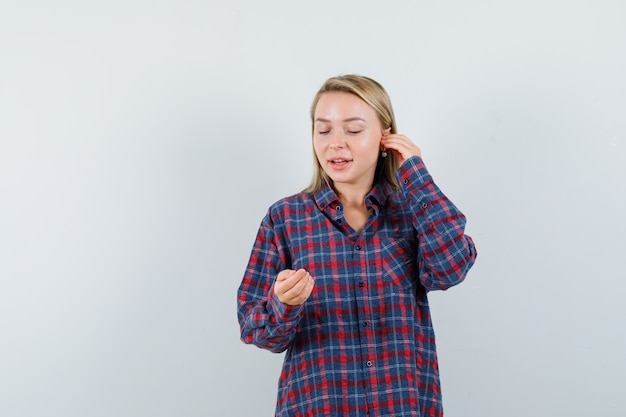 Blondynka w kraciastej koszuli, trzymając dłoń na uchu i udając, że patrzy na telefon i patrzy optymistycznie, widok z przodu.