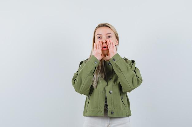 Blondynka w kurtce, spodniach mówiących w tajemnicy i wyglądająca na zmartwioną, widok z przodu.