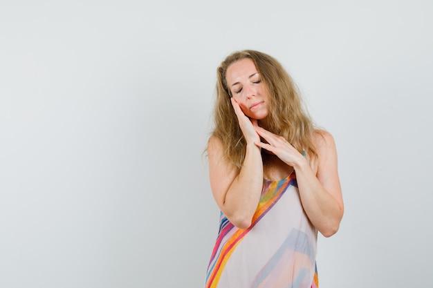 Blondynka w letniej sukience, opierając policzek na dłoni i wyglądająca spokojnie
