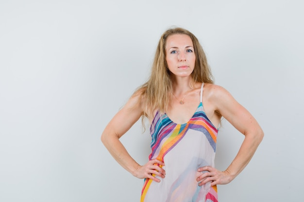 Blondynka w letniej sukience, trzymając się za ręce w talii i wyglądająca pewnie