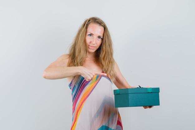 Blondynka w letniej sukience, wskazując na obecne pudełko i patrząc wesoło