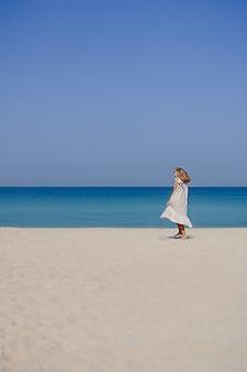 Blondynka w lnianej sukience maxi z rozwianymi włosami, skacząca i tańcząca na piaszczystej plaży na tle błękitnego nieba i morza. długi strzał