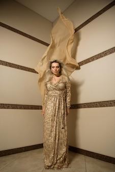 Blondynka w modelu plus rozmiar w rogu pokoju z dużym ciętym materiałem