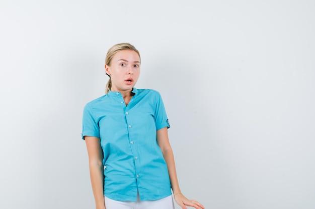 Blondynka w niebieskiej bluzce, białych spodniach, wzruszając ramionami na białym tle