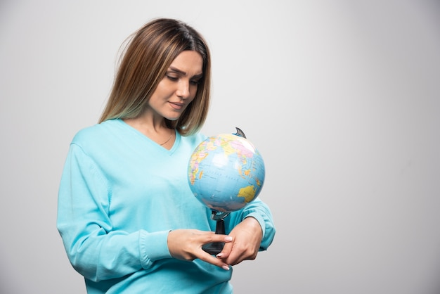 Blondynka w niebieskiej bluzie trzyma kulę ziemską i uważnie sprawdza mapę ziemi.