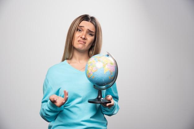 Blondynka w niebieskiej bluzie trzyma kulę ziemską i wygląda na niepewną i zdezorientowaną.