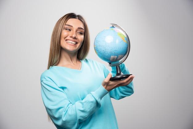 Blondynka w niebieskiej bluzie trzyma kulę ziemską, zgadywanie lokalizacji i dobrą zabawę.