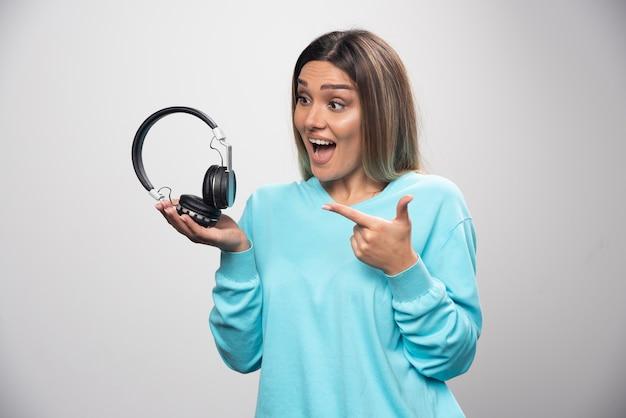 Blondynka w niebieskiej bluzie trzyma słuchawki i przygotowuje się do noszenia ich do słuchania muzyki.