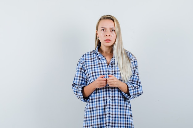 Blondynka w niebieskiej kraciastej koszuli w kratkę trzymająca się za ręce, grająca na konsoli i wyglądająca na zmęczoną, widok z przodu.