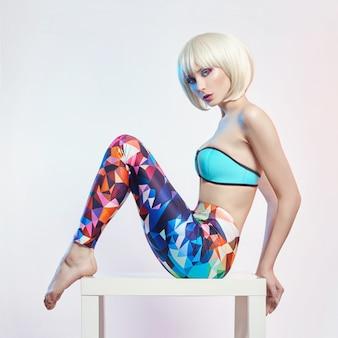Blondynka w niebieskim trykocie i legginsach z jasnym kontrastowym makijażem siedzi na stole