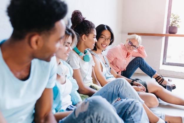 Blondynka w okularach i różowej koszuli siedzi na podłodze i z zainteresowaniem patrzy na swoich międzynarodowych kolegów z klasy. portret studentów odpoczywających w kampusie.