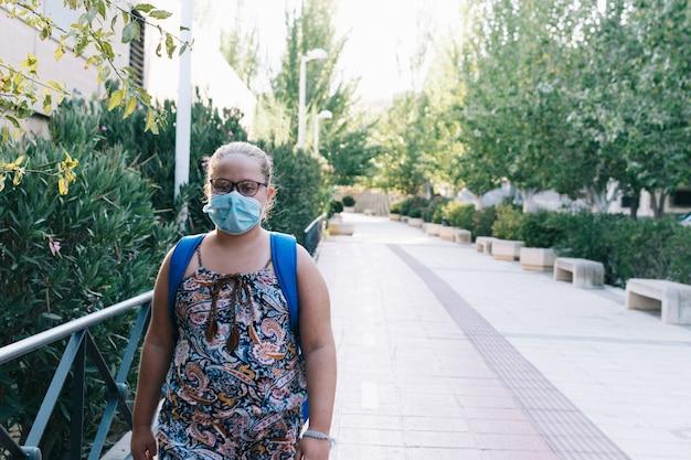 Blondynka w okularach, niebieskim plecaku i masce na twarz w drodze do szkoły