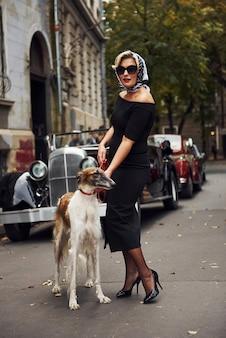 Blondynka w okularach przeciwsłonecznych iw czarnej sukience w pobliżu starego rocznika klasyczny samochód z psem.