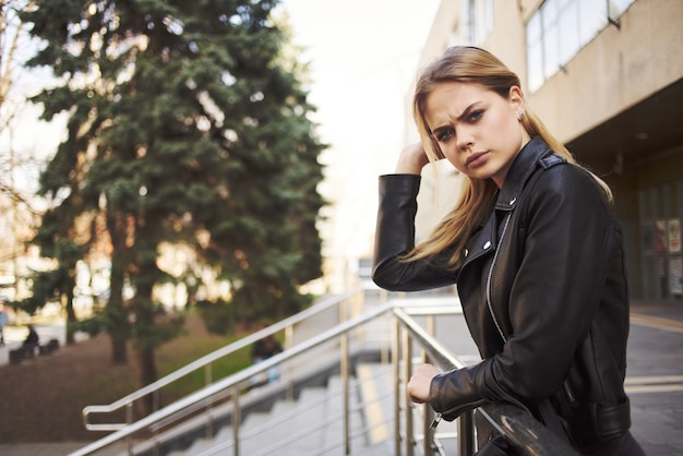 Blondynka w okularach przeciwsłonecznych skórzana kurtka chodząca na zewnątrz moda lato