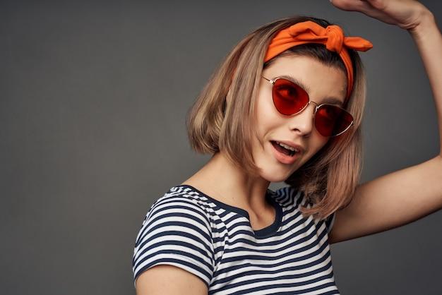 Blondynka w okularach przeciwsłonecznych tshirt w paski nowoczesny styl na białym tle