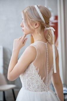 Blondynka w pięknej białej sukni ślubnej. panna młoda kobieta czeka na pana młodego przed ślubem