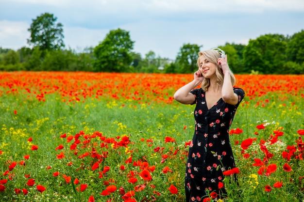 Blondynka w pięknej sukni ze słuchawkami w polu maki w okresie letnim