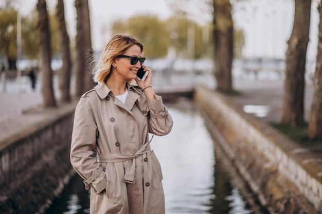Blondynka w płaszczu na zewnątrz w parku za pomocą telefonu