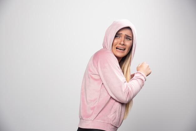 Blondynka w różowej bluzie robi przerażoną minę w bluzie z kapturem.