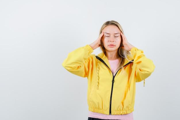 Blondynka w różowej koszulce i żółtej kurtce kładzie ręce na skroniach, zamyka oczy i wygląda na spokojną