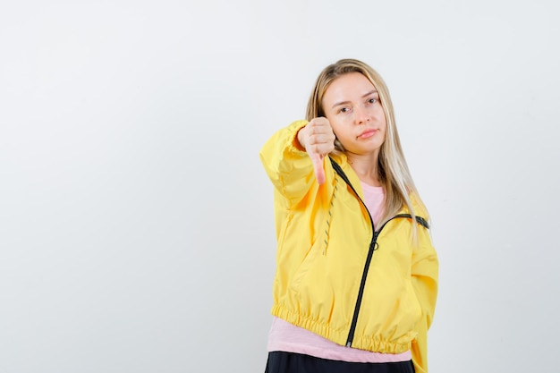 Blondynka w różowej koszulce i żółtej kurtce pokazując kciuk w dół i patrząc poważnie down