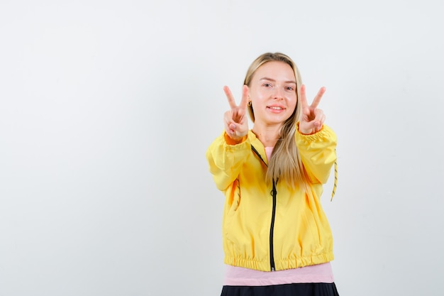 Blondynka w różowej koszulce i żółtej kurtce pokazuje gesty pokoju i wygląda na szczęśliwego