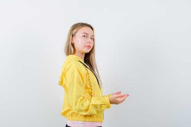 Blondynka w różowej koszulce i żółtej kurtce, rozciągając ręce, trzymając coś i wyglądając poważnie