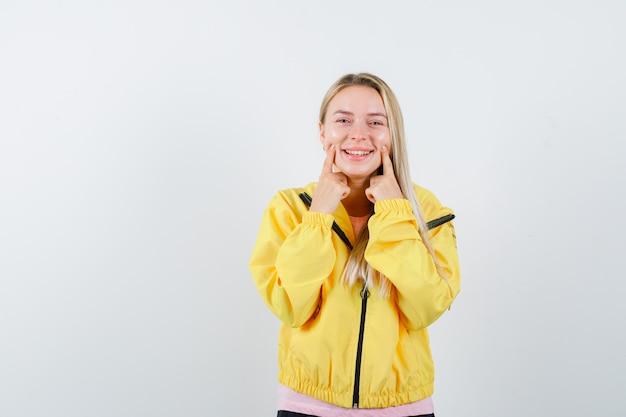Blondynka w różowej koszulce i żółtej kurtce trzymając palce wskazujące w pobliżu ust, zmuszając do uśmiechu i wyglądając na szczęśliwego
