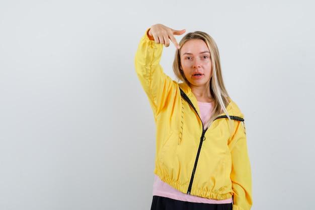 Blondynka w różowej koszulce i żółtej kurtce, wskazując na aparat palcem wskazującym i wyglądająca poważnie