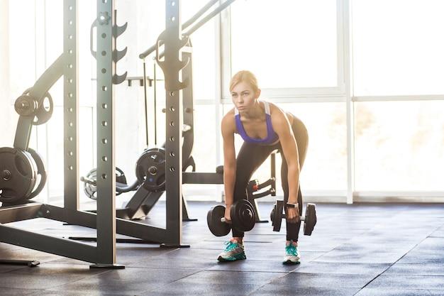 Blondynka w siłowni, pochylenie z hantlami. zdjęcia studyjne