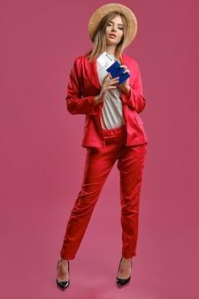 Blondynka w słomkowym kapeluszu, biała bluzka, czerwone spodnie i czarne szpilki trzyma paszport