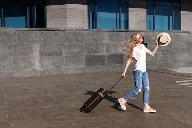 Blondynka w słomkowym kapeluszu i walizce do podróży jeździ po mieście w letnią podróż po świecie