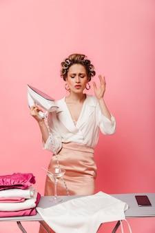 Blondynka w spódnicy i białej bluzce trzyma żelazko na różowej ścianie