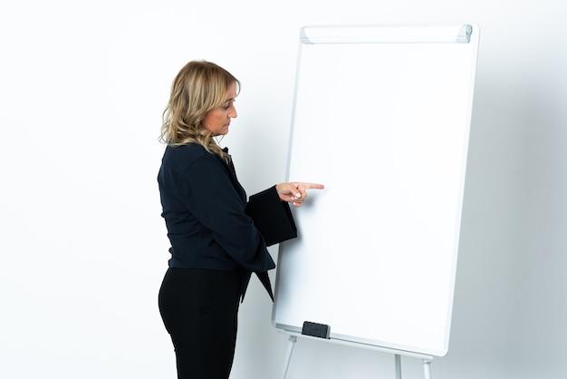Blondynka w średnim wieku na białym tle, przedstawiająca prezentację na białej tablicy i wskazując ją