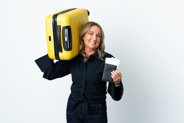 Blondynka w średnim wieku na odosobnionym białym tle na wakacjach z walizką i paszportem