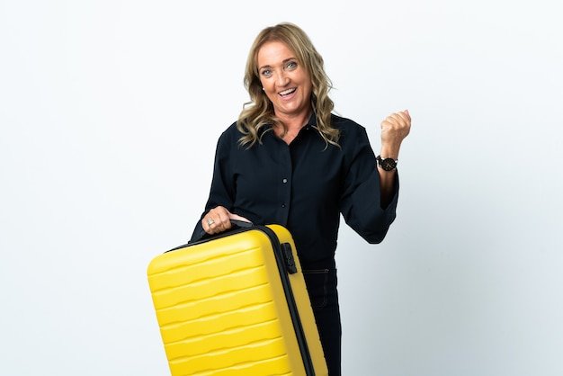 Blondynka w średnim wieku na odosobnionym białym tle na wakacjach z walizką podróżną
