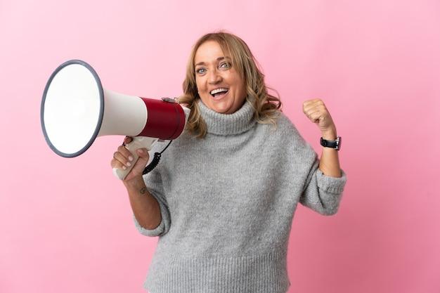 Blondynka w średnim wieku na odosobnionym różowym tle krzyczy przez megafon i wskazuje bok