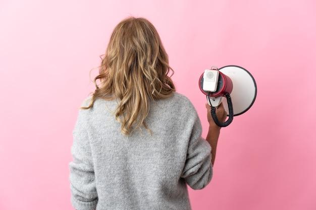 Blondynka w średnim wieku na odosobnionym różowym tle, trzymająca megafon w pozycji z tyłu