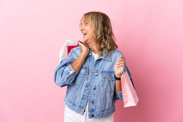 Blondynka w średnim wieku na odosobnionym różowym tle trzymająca torby na zakupy i uśmiechnięta