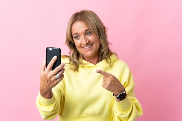 Blondynka w średnim wieku na odosobnionym różowym tle, używająca telefonu komórkowego i wskazującego go