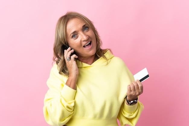 Blondynka w średnim wieku na różowym tle, prowadząca rozmowę przez telefon komórkowy i trzymająca kartę kredytową
