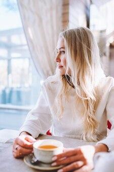 Blondynka w średnim wieku siedzi sama w kawiarni przy filiżance kawy i patrzy w okno.