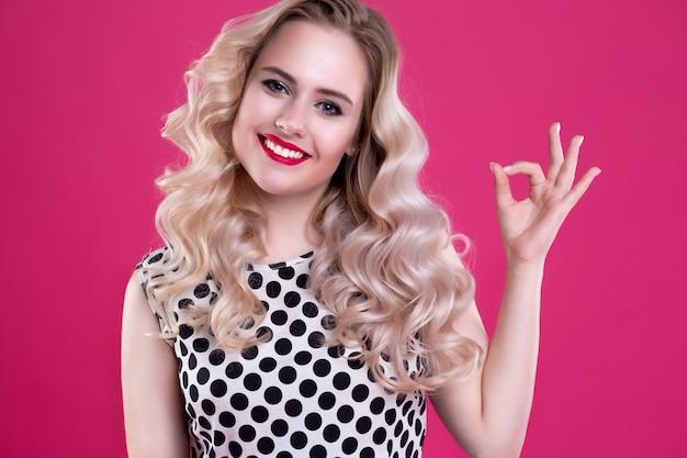 Blondynka w stylu pin-up pokazuje znak ok