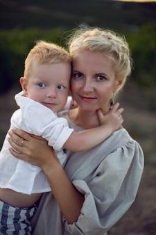 Blondynka w sukience trzyma chłopca w ramionach w winnicy podczas zachodu słońca