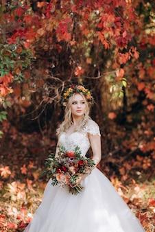 Blondynka w sukni ślubnej w jesiennym lesie na tle dzikich czerwonych winogron