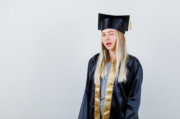 Blondynka w sukni ukończenia szkoły i czapce stoi prosto, mrugając i pozując do kamery i wyglądając na szczęśliwą