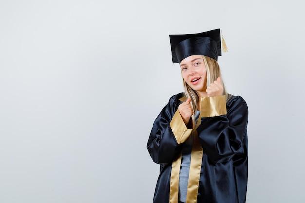 Blondynka w sukni ukończenia szkoły i czapce stoi w pozie bokserki i wygląda na szczęśliwą