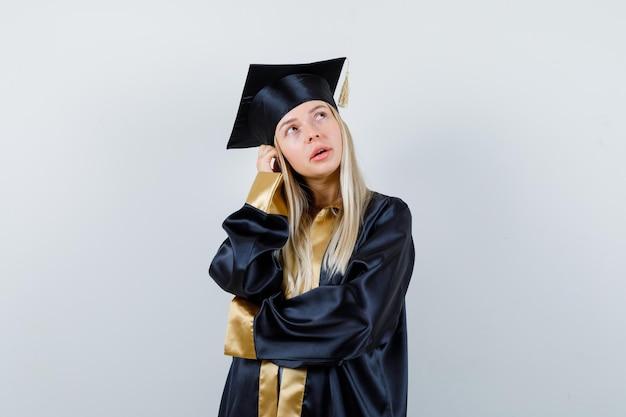 Blondynka w sukni ukończenia szkoły i czapce stoi w pozie myślącej i wygląda na zamyśloną
