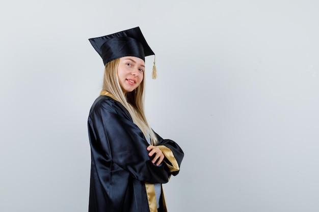 Blondynka w sukni ukończenia szkoły i czapce stoi ze skrzyżowanymi rękami, patrząc przez ramię i wyglądając na szczęśliwą